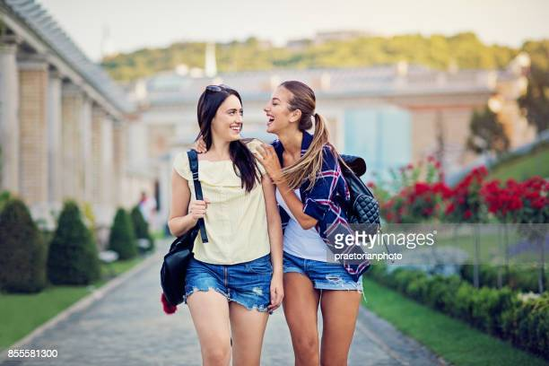 Happy girlfriends are walking in the park and making fun together