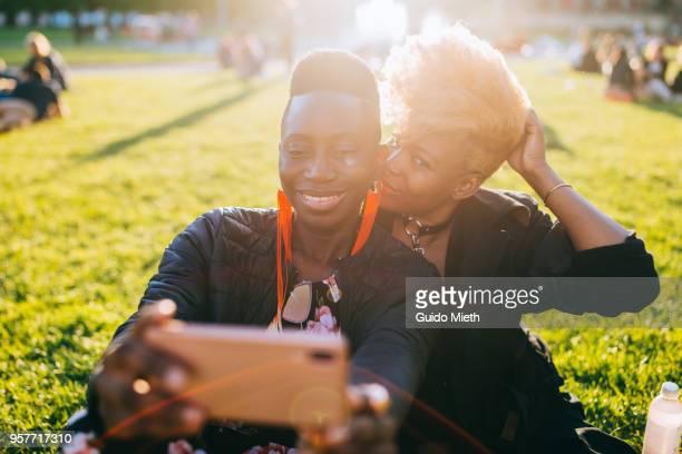 Happy girlfriends doing selfie in sunlight.