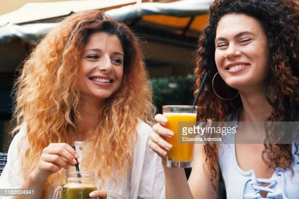 Happy girlfriends drinking juice