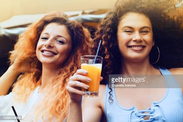 Happy girlfriends drinking orange juice