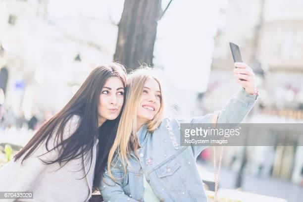 Happy girlfriends, taking selfies, having fun outdoors. Belgrade, Serbia, Europe
