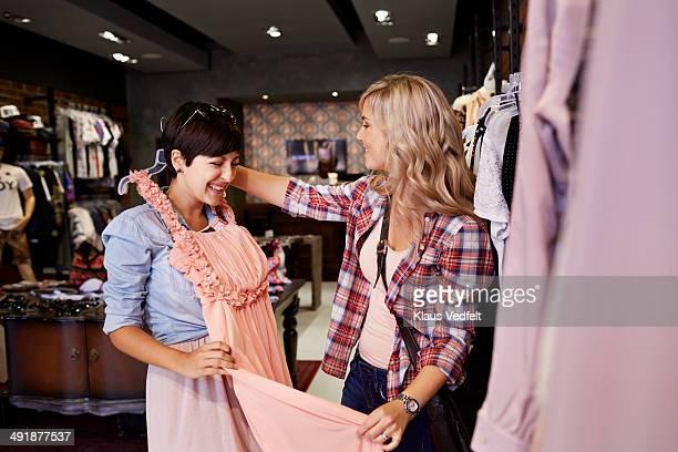 Happy girlfriends trying dress in fashion shop