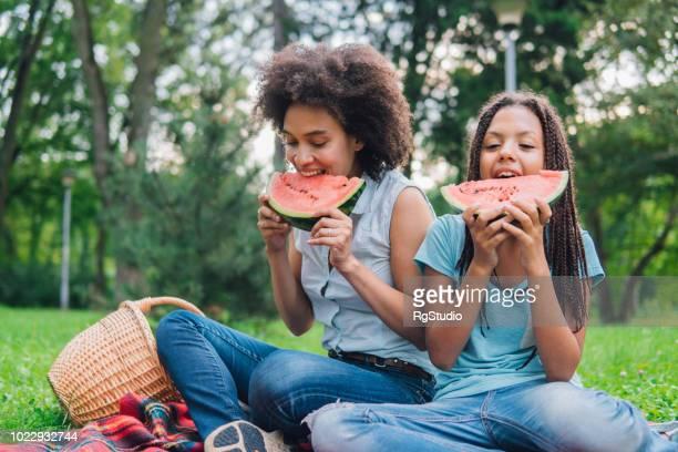 meninas felizes comendo melancia em um piquenique - fruta - fotografias e filmes do acervo