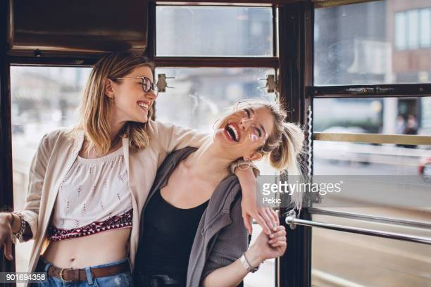 happy girls hugging in tramcar - solo donne foto e immagini stock