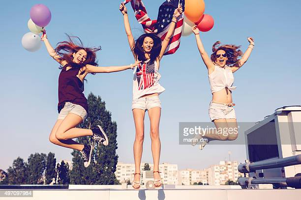Happy girls jumping on the rooftop
