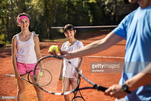 Happy girls learning to play tennis with help of instructor.