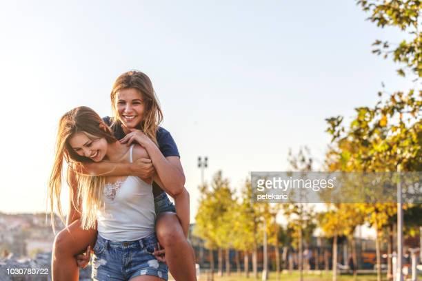 fille d'enfants heureux dans le parc - ados lesbiennes en couple photos et images de collection