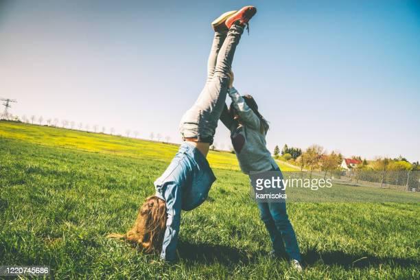 glückliche mädchen spielen auf der sommerwiese - versuchen handstand - bewegungsaktivität stock-fotos und bilder