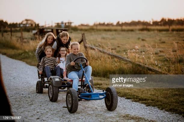 happy girls riding go-kart on dirt road - gotland bildbanksfoton och bilder