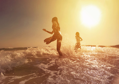 Happy girls running to the sea on a beautiful sunset - gettyimageskorea
