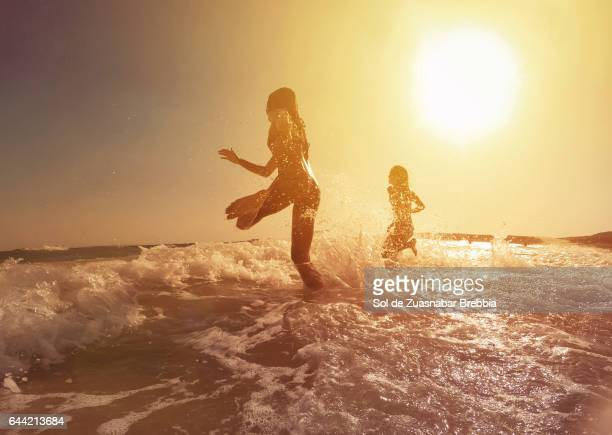 happy girls running to the sea on a beautiful sunset - calientes fotografías e imágenes de stock