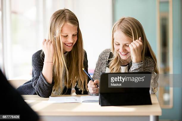 Happy girls smiling while looking at book in classroom