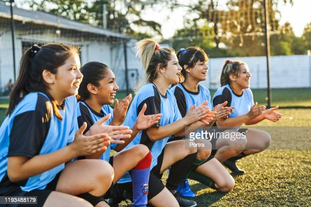 happy girls soccer players applauding during match - football team stock pictures, royalty-free photos & images