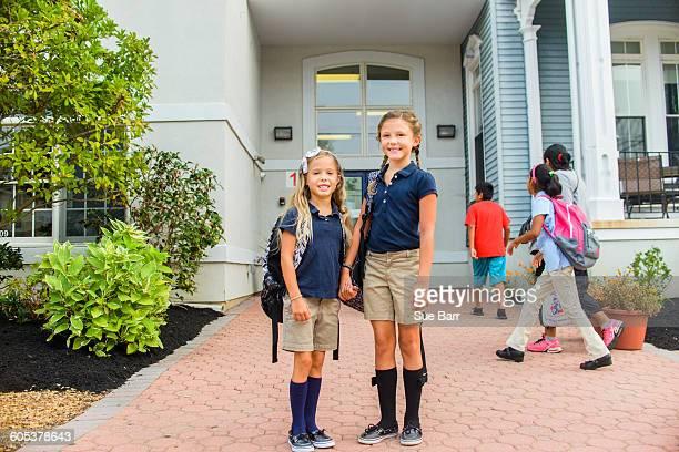 Happy girls standing in front of school