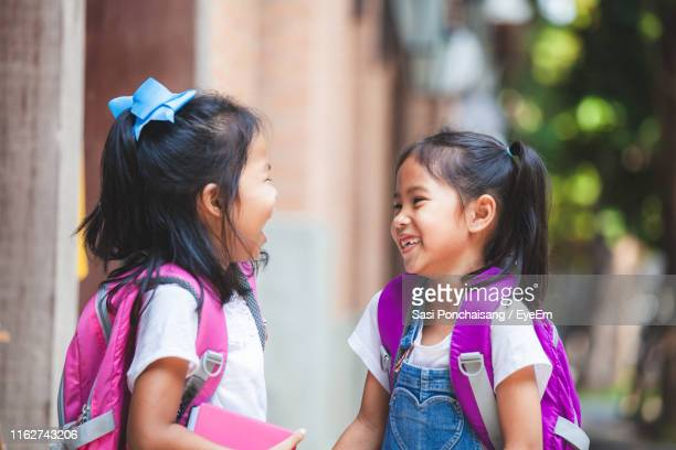 happy girls standing outdoors - children only stock pictures, royalty-free photos & images