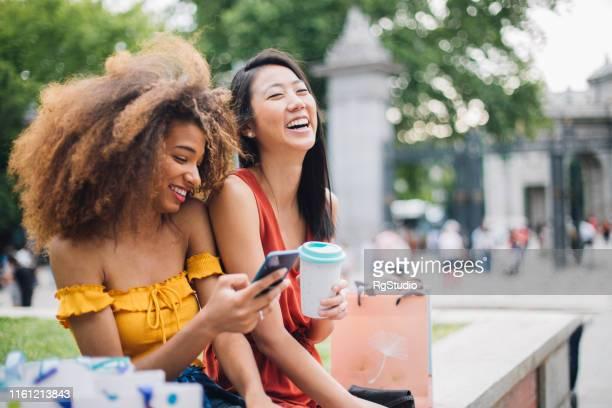 快樂的女孩使用手機戶外 - 女裝 個照片及圖片檔