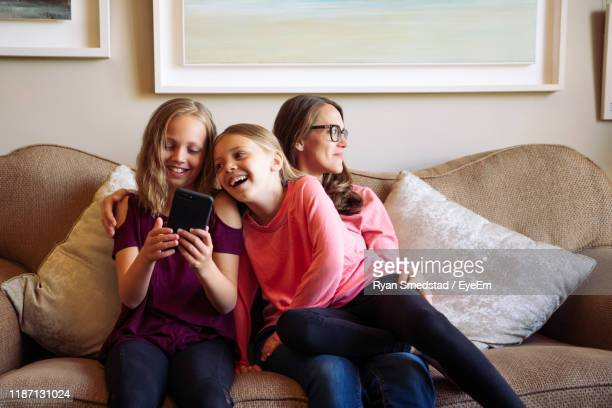 happy girls using phone while sitting on sofa - pre adolescent child stock pictures, royalty-free photos & images