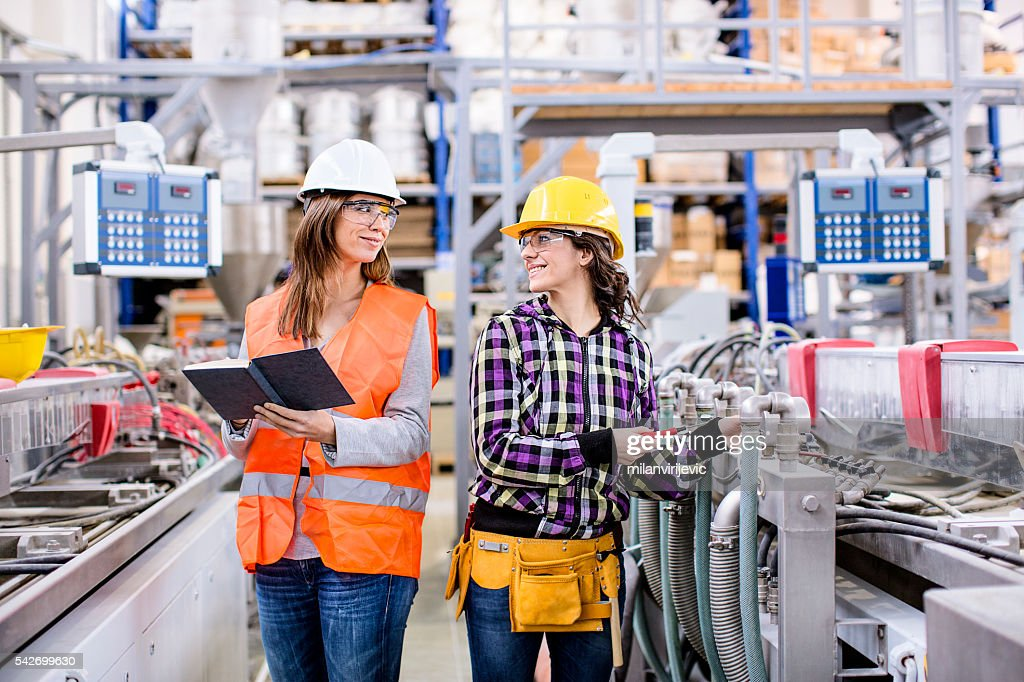 Happy girls working together in factory : Stock Photo