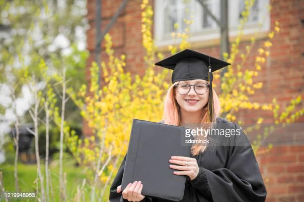 happy graduate outdoors - diploma foto e immagini stock