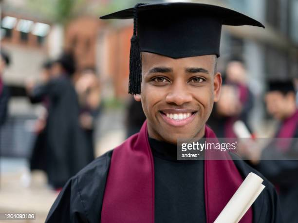 happy graduating student holding his diploma - alumni stock pictures, royalty-free photos & images
