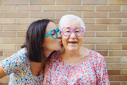 Happy granddaughter and grandmother wearing heart-shaped glasses - gettyimageskorea