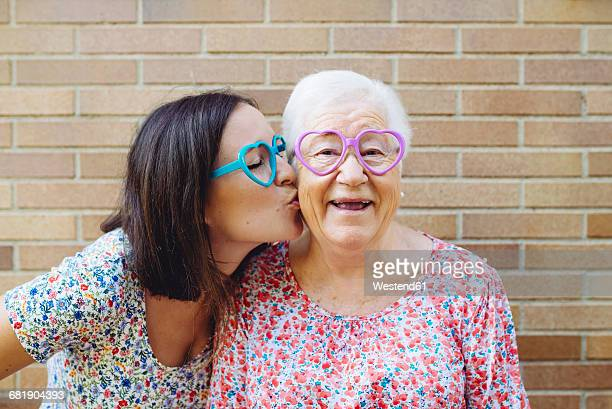Happy granddaughter and grandmother wearing heart-shaped glasses