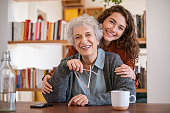 cheerful young woman embracing senior mother
