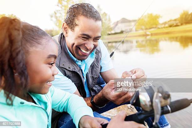 Happy grandfather and granddaughter fish together