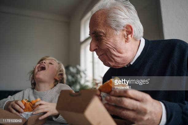 happy grandfather and grandson eating burger together at home - speisen stock-fotos und bilder