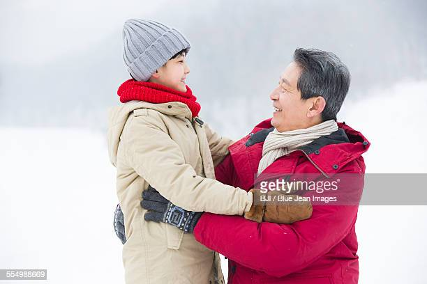 Happy grandfather and grandson embracing on the snow