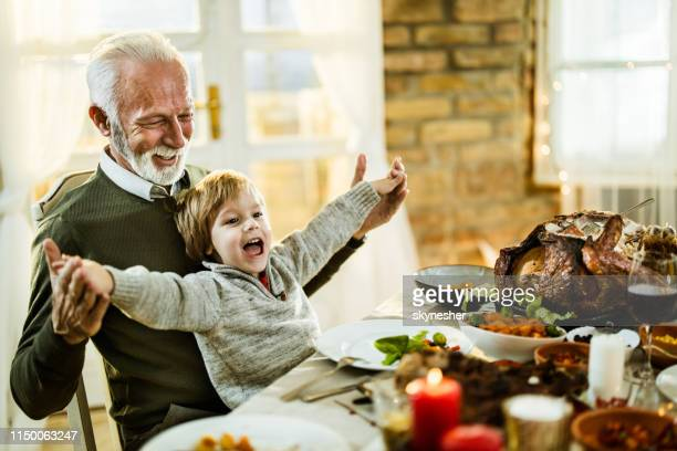 happy grandfather and grandson having fun during thanksgiving lunch at home. - grandfather stock pictures, royalty-free photos & images