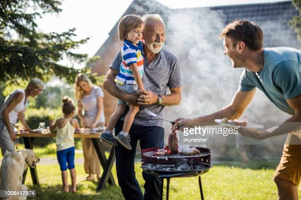 Happy grandfather and grandson talking to young father preparing barbecue in the backyard.
