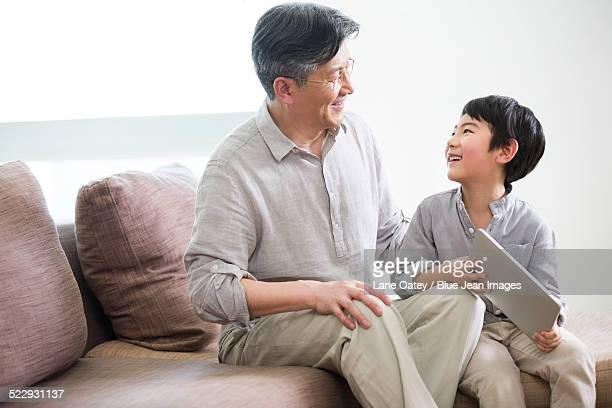 happy grandfather and grandson with digital tablet - tidy room stock pictures, royalty-free photos & images