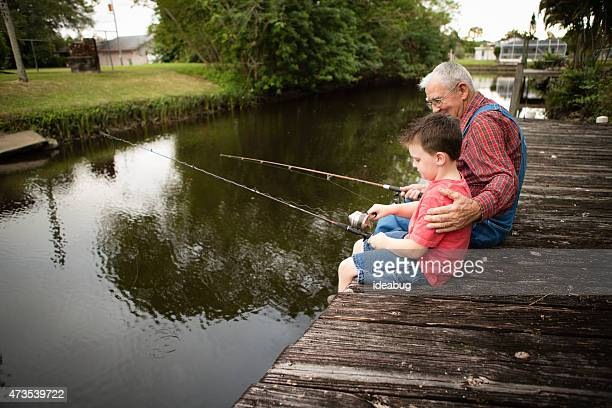 Happy Grandfather and Great Grandson Fishing on Dock