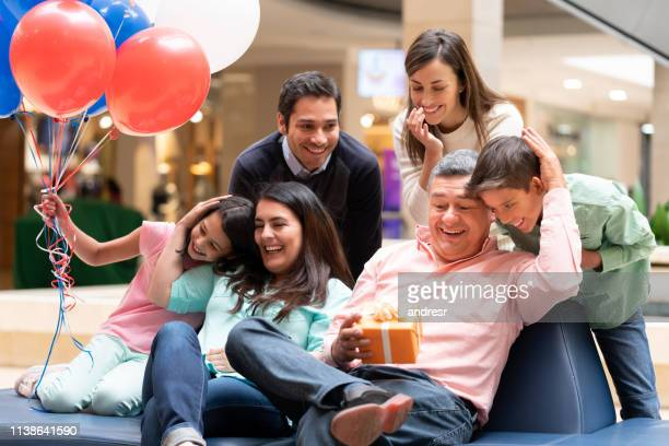 happy grandfather celebrating father's day with his family at the mall - fathers day stock pictures, royalty-free photos & images