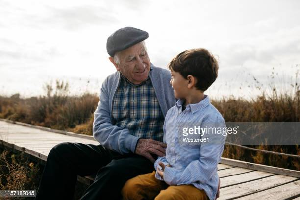 happy grandfather sitting with his grandson on boardwalk looking at each other - hommes seniors photos et images de collection