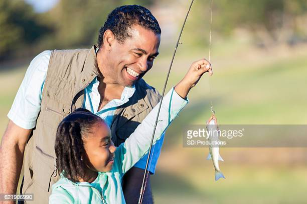 Happy grandfather teaches granddaughter to fish