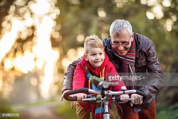 Glücklich Großvater beizubringen seine Enkel, wie Radfahren.