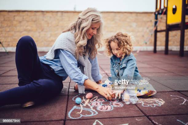 happy grandmother and cute granddaughter drawing with chalk at park - chalk art equipment stock pictures, royalty-free photos & images