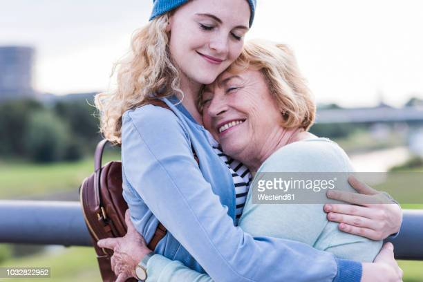 happy grandmother and granddaughter hugging each other - jung geblieben stock-fotos und bilder