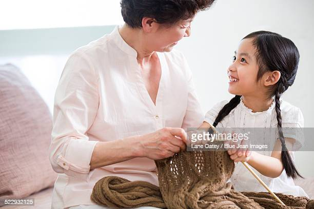 Happy grandmother and granddaughter knitting in living room