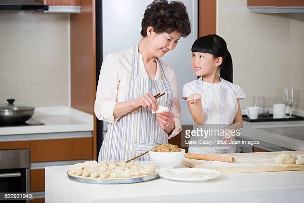 happy grandmother and granddaughter making dumplings - 中国北東部 ストックフォトと画像