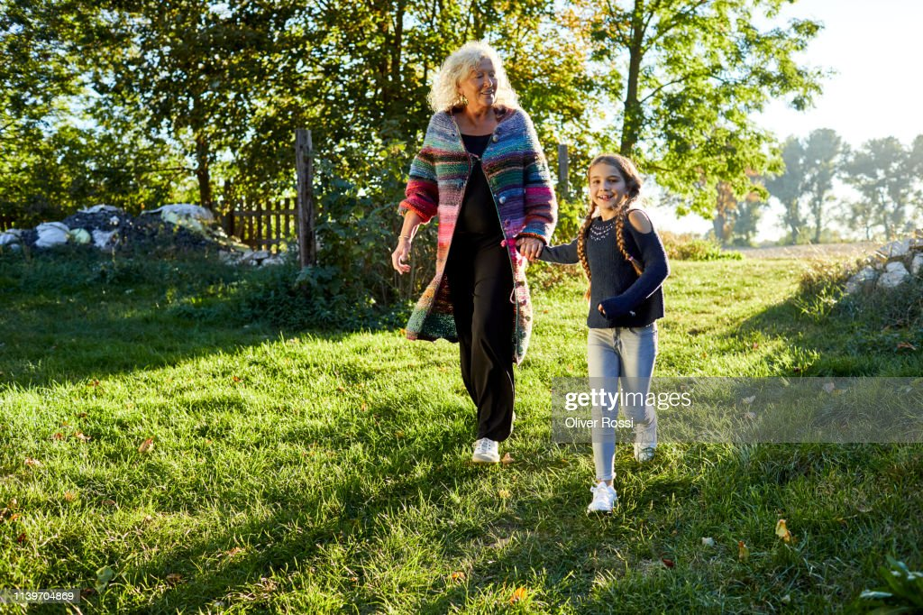Happy grandmother and granddaughter walking in garden : Stock Photo