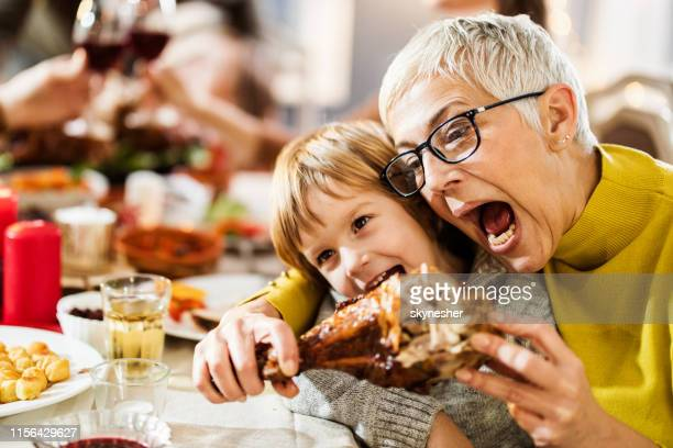 happy grandmother and her grandson having fun while biting turkey leg at home. - kids thanksgiving stock pictures, royalty-free photos & images