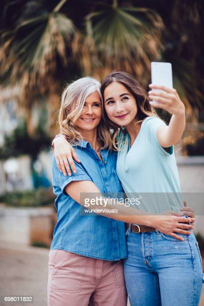 Happy grandmother and teenage granddaughter taking selfies on summer vacations