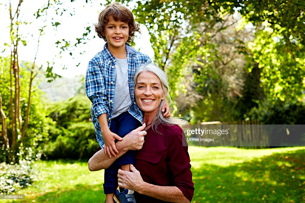 Happy grandmother carrying grandson at park : Stock Photo