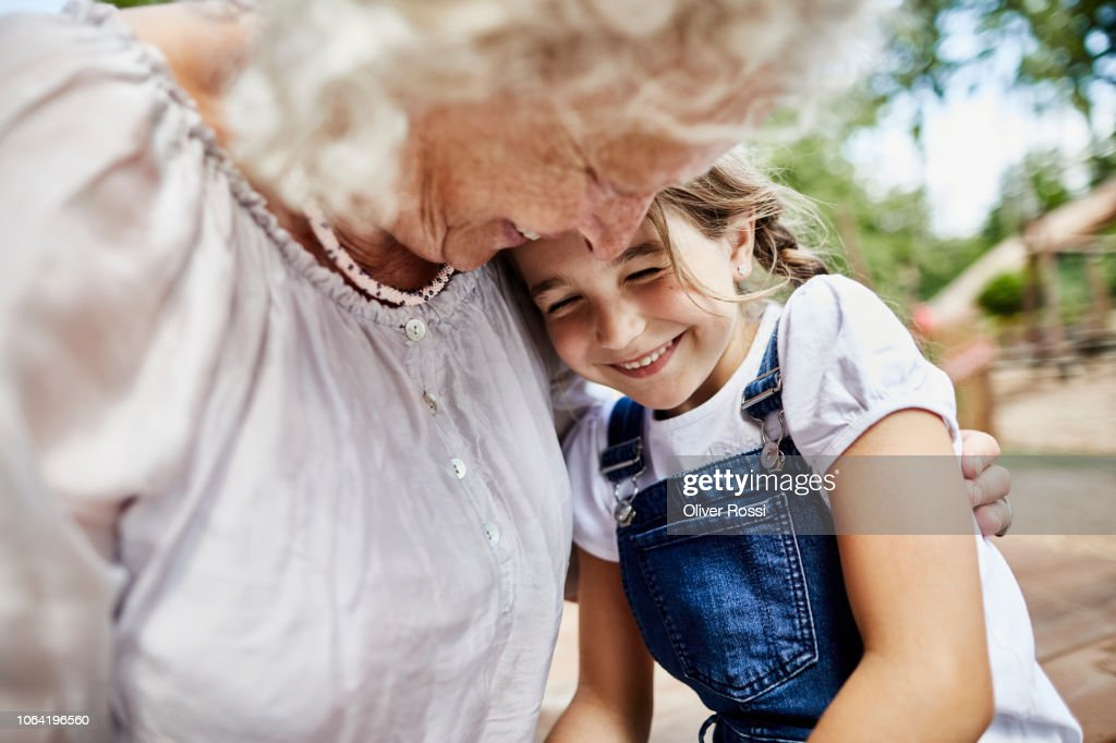 Happy grandmother embracing granddaughter outdoors : Stock Photo