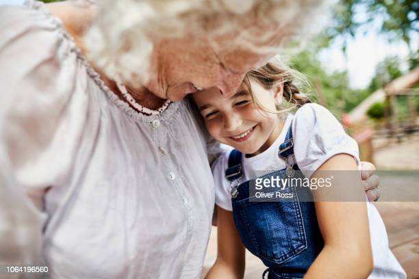 happy grandmother embracing granddaughter outdoors - cuidado fotografías e imágenes de stock