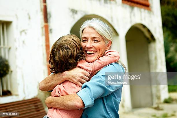 happy grandmother embracing grandson in yard - grandmother stock pictures, royalty-free photos & images