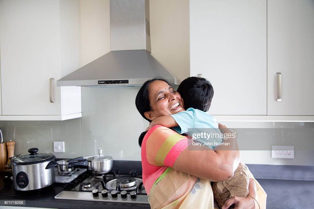Happy Grandmother hugging young grandson at home : Stock Photo